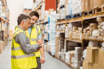 two men looking at clipboard in warehouse