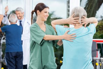 nurse helping elderly patient exercise
