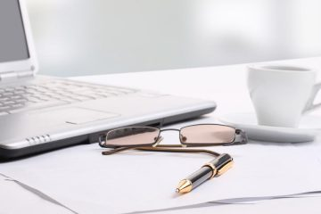 glasses, cup, pen, paper and laptop on desktop