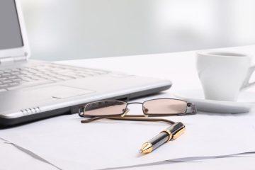 glasses, cup, pen, paper and laptop on desktop