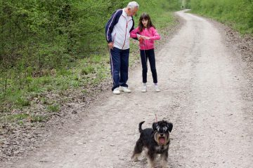 older man and young girl walking a dog on unpaved road