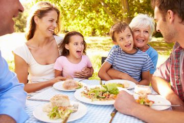 family of grandparents, parents and children eating outside